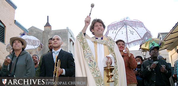 November 16, 2005. Jazz musician and composer Irvin Mayfield leads a second line parade, the first of its kind following Hurricane Katrina, from St. Louis Cemetery #1 through New Orleans' French Quarter, alongside the Very Rev. David Allard DuPlantier, dean of Christ Church Cathedral New Orleans. © The Archives of the Episcopal Church (DFMS).
