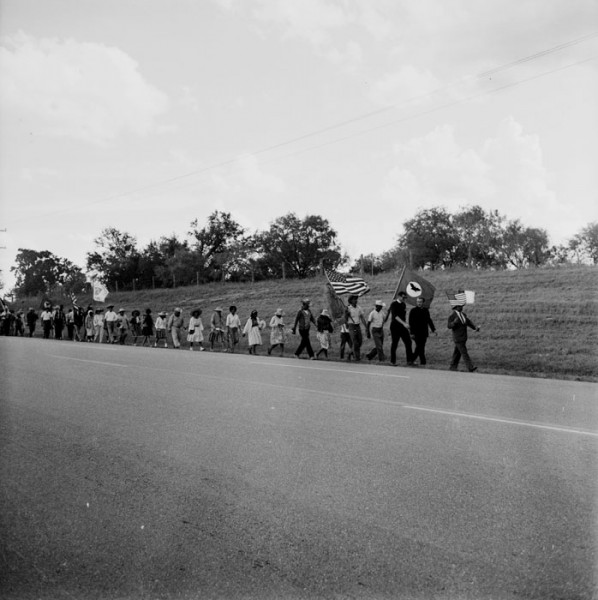 "The Rio Grande Valley Farm Workers March (""La Marcha"") was among the major events in the Latino movement for economic justice in Texas during the 1960s.  The impetus for the march developed after efforts to gain decent wages for farm laborers in Starr County had failed in 1966. Rev. James Novarro, pastor of Kashmere Baptist Temple in Houston and co-chairman of the march, leads the marchers – who are on their way to the capitol in Austin -- along U. S. Highway 181 near Floresville, August 24, 1966. Image # E-0012-187-B-02, San Antonio Express-News Photograph collection, MS 360, University of Texas San Antonio Libraries Special Collections."